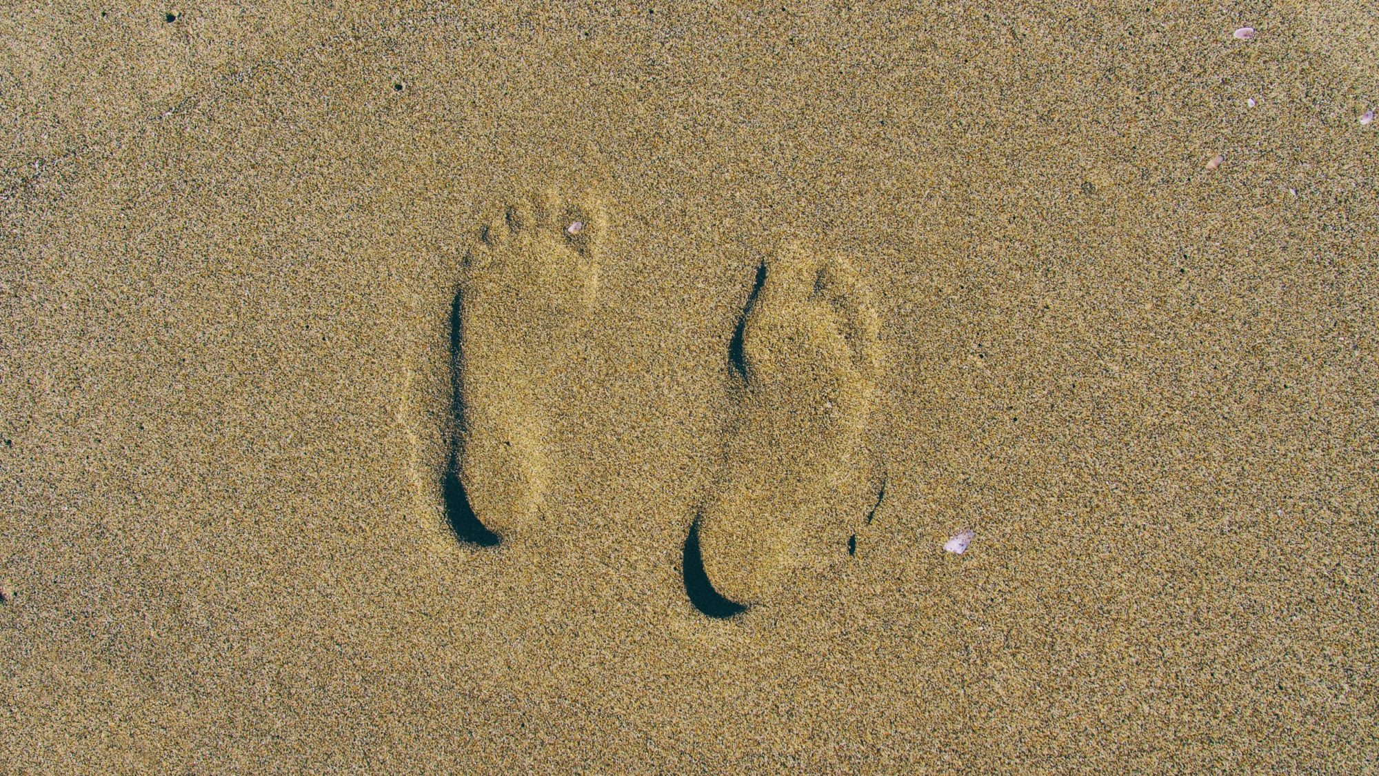 Two footprints in the sand.
